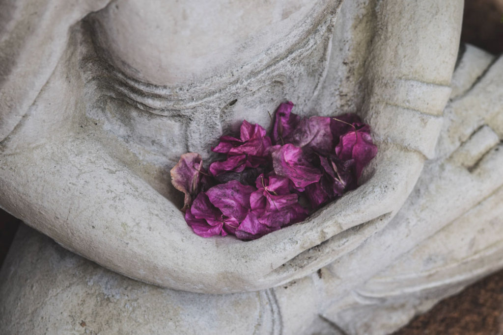 Seated meditative statue holding purple flower pedals.